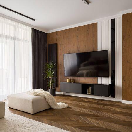 Elegant gestaltetes Wohnzimmer mit großem Fernsehbildschirm, Holzboden und -wand Standard-Bild