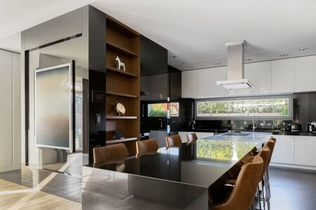 Elegant and spacious kitchen in black and white, with dining area for eight