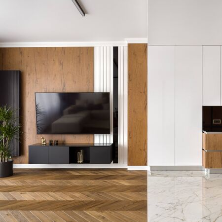 Apartment with wooden floor and wall in living room and marble floor in kitchen