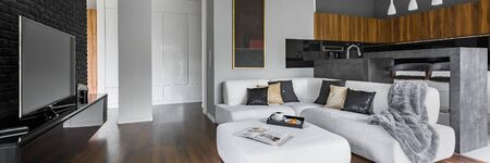 Panorama of spacious and elegant apartment with living room with white, corner sofa and tv open to kitchen