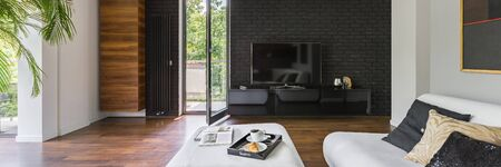Panorama of elegant living room with tv on black brick wall, wooden floor and balcony door Imagens