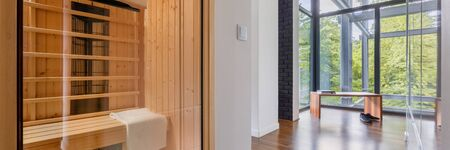 Panorama of finnish home sauna in modern apartment with glassed walls in corridor with wooden bench