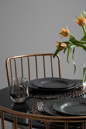 Stylish, black dining table with tableware for two and two copper color chairs