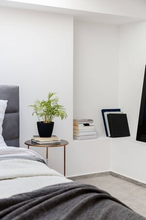 Simple bedroom with round bedside table and books on shelf in wall Banque d'images