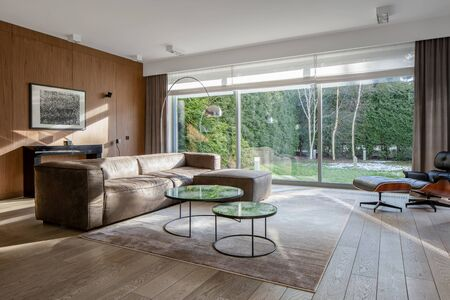 Elegant living room with window wall, wooden floor and wall and big corner sofa