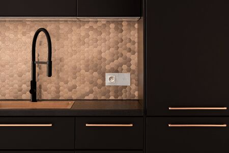 Stylish kitchen with copper sink, handles and hexagonal wall tiles and black faucet, cupboards, drawers, countertop and black built-in fridge