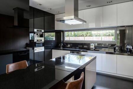 Moderne schwarz-weiße Küche mit Kücheninsel und Esstisch