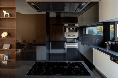 Elegant kitchen with mirrored wall and induction hob with five burners