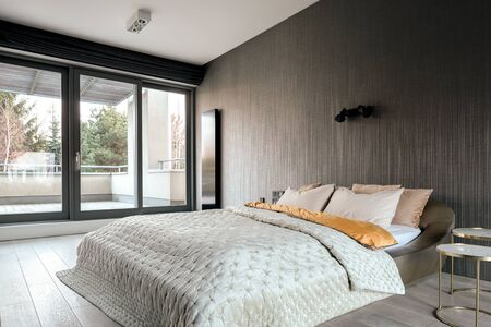 Elegant bedroom with double bed, vinyl wallpaper and balcony behind window wall