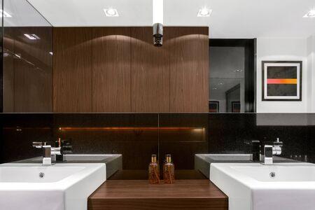 Elegant bathroom with two washbasins, big mirror and wooden furniture
