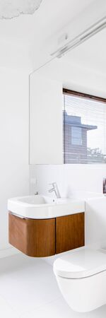 Vertical panorama of white bathroom with big mirror and wooden chest with drawer under washbasin