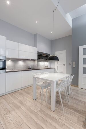 Elegante Küche mit grauen Wänden und weißen Möbeln und schlichtem Esstisch mit stilvollen Stühlen in der Mitte