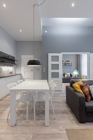 Modern apartment interior in white and gray, with wooden floor and ceiling lights Stockfoto