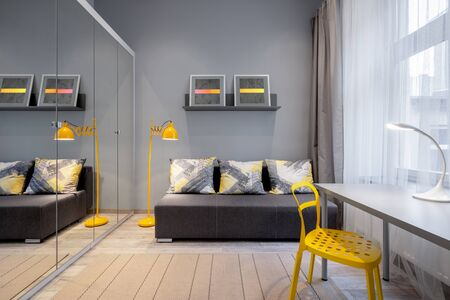 Simple room with gray wall and couch, desk with yellow chair and wardrobe with mirrored doors