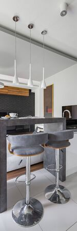 Vertical panorama of elegant kitchen interior with stylish kitchen island with gray countertop and two chairs Archivio Fotografico