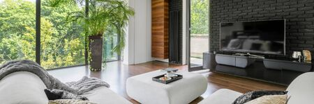 Panorama of living room with tv on black brick wall, ottoman for coffee table and big windows Archivio Fotografico