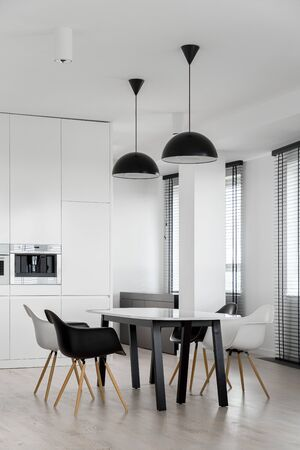 Stylish dining area with modern table and chairs in kitchen with many windows Banco de Imagens
