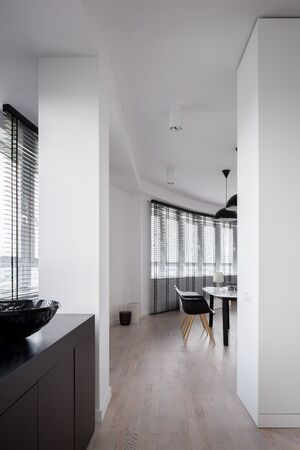 Dining room and corridor in open apartment with curved wall and many windows with blinds