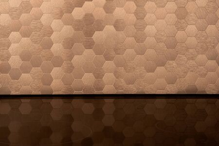 Close-up on elegant golden, hexagonal wall tiles and black induction hob with mirrored surface Foto de archivo