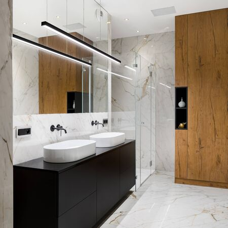 Elegant bathroom in white marble tiles on floor and walls and with black chest of drawers under two, oval washbasins