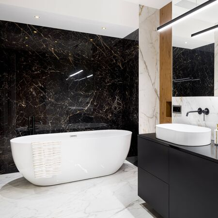Luxury and stylish bathroom with black and white marble tiles and big oval bathtub