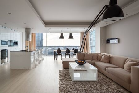 Modern and elegant apartment with big corner sofa, stylish black lamp, luxury kitchen area and dining table in one spacious room with big window and amazing city view Banco de Imagens