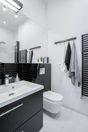 Black and white bathroom with big mirror and black chest of drawers