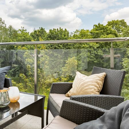 Stylish balcony with elegant rattan furniture, beige decorations, glass balustrade and green forest view