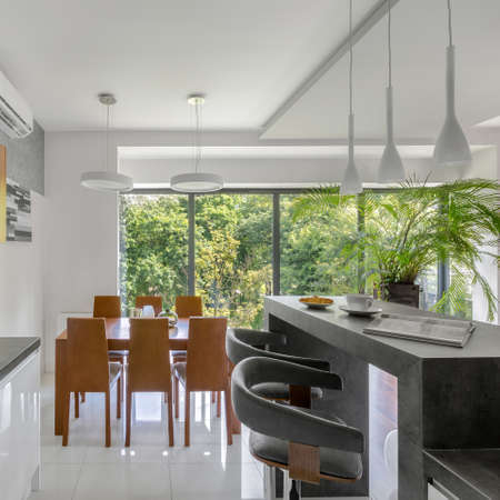 Elegant kitchen with gray kitchen island with two tall chairs open to dining area with simple wooden table and chairs and window wall