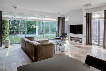 Elegant living room with stylish furniture, wooden floor, dark dining table and window wall with garden view