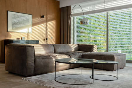 Elegant living room with big corner sofa, two modern coffee tables and silver lamp with big windows with garden view