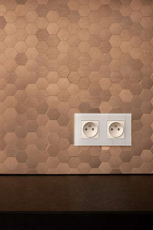 Simple white electrical sockets in stylish wall in copper tiles in hexagonal shape and black countertop