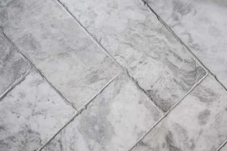 Close-up on modern gray, rectangle shaped floor tiles put in herringbone pattern