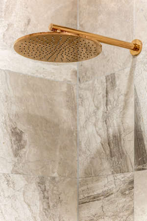 Close-up on stylish golden shower head in wall with elegant beige marble tiles