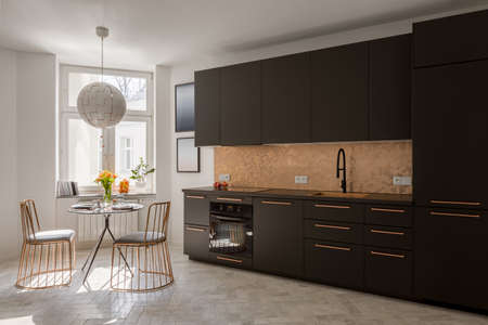 Modern black kitchen with stylish copper details with new dining table and two, elegant copper chairs