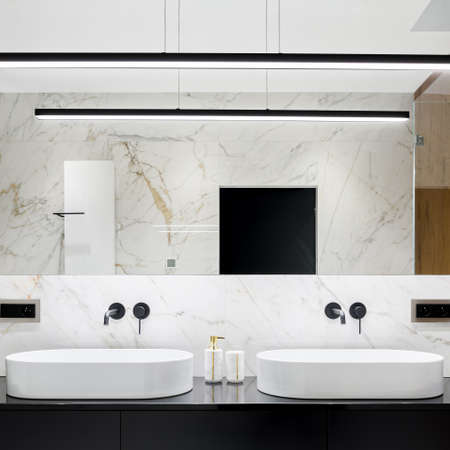 Elegant bathroom with two white and oval washbasins and big mirror with led lighting and marble tiles