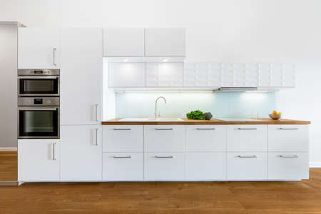 Modern kitchen with white furniture, wooden floor and countertop and build in oven and microwave
