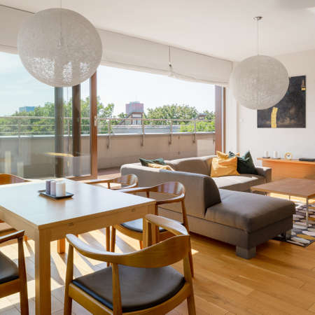 Modern living room with big window open to terrace, wooden dining table and hardwood floor
