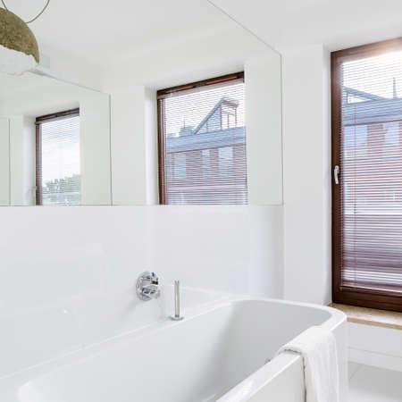 Elegant white bathroom interior with big window, mirror wall and stylish bathtub