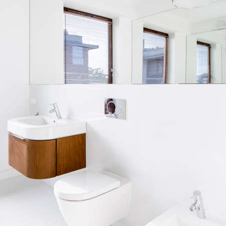 Modern white bathroom with mirror and wooden chest with drawer under small washbasin Reklamní fotografie