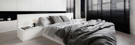 Panorama of stylish bedroom designed in white with big windows with black blinds Banque d'images