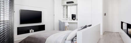 Panorama of elegant and stylish bedroom in white with dressing table in wardrobe