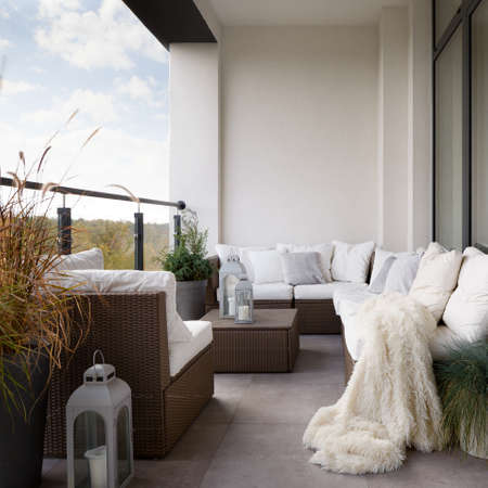 Home balcony with elegant decorations, stylish rattan furniture and natural plants