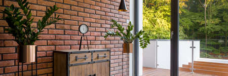 Panorama of stylish room with brick wall, balcony, big window and wooden dresser