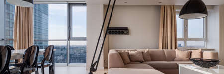 Panorama of luxury living room with black lamp above elegant corner sofa, window wall and amazing view and dining table with chairs