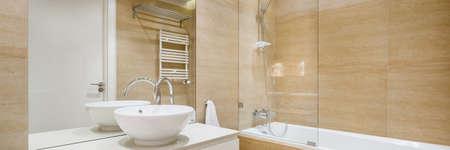 Panorama of elegant bathroom with big bathtub, mirror wall, stylish washbasin and with beige tiles