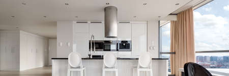 Panorama of black and white luxury kitchen with kitchen island and stylish chairs in spacious apartment with big window walls and amazing view