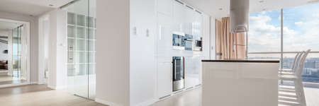 Panorama of white shiny and luxury kitchen, spacious corridor and elegant interior design in apartment with amazing view Standard-Bild