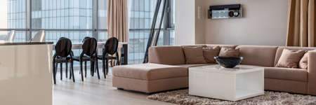 Panorama of elegant, beige corner sofa with white coffee table in room with dining area and window wall 版權商用圖片