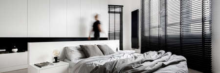 Panorama of luxury bedroom interior in black and white, with big windows with blinds and person walking in it